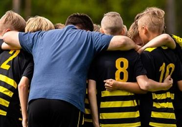 A picture of a football team and their coach, gathered ina huddle.
